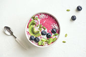 Smoothie bowl with fresh berries, fruits, seeds and coconut cream for healthy vegan vegetarian diet breakfast. Acai blueberry coconut smoothie bowl.