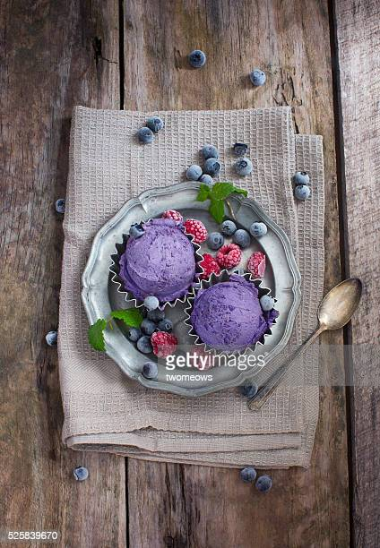 Blueberry ice cream ball with fresh blueberry on white wooden table top.
