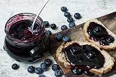 blueberry jam in a jar with two sweet sandwiches and ripe berries on white rustic wooden background. close up