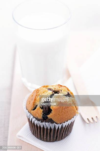 Blueberry muffin and wooden fork on napkin beside glass of milk, close-up