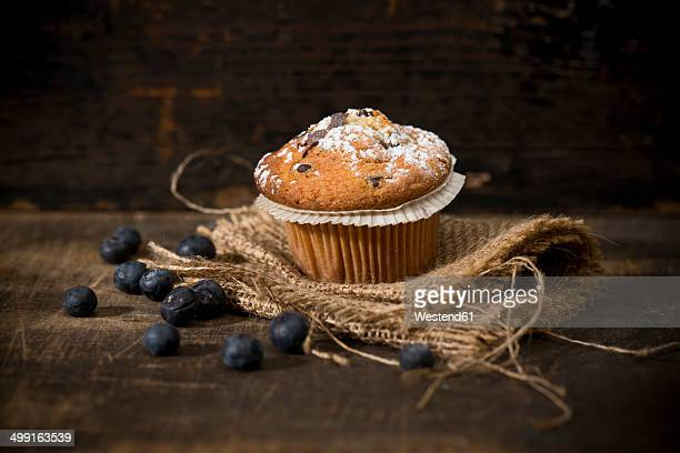Blueberry muffin, jute and blueberries on wooden table