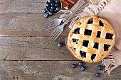 Rustic homemade blueberry pie with lattice pastry. Top view scene. Corner border with copy space over a rustic wood background.