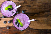 Blueberry smoothies on wooden floor from top view.
