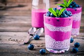 Blueberry smoothies with chia pudding in glass with fresh berries and mint on wooden background