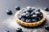 Blueberry tartlet, pie, tart with vanilla custard. Slate stone background. Copy space