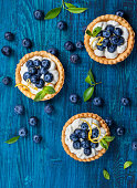 Delicious Blueberry tartlets with vanilla cream on  blue wooden background. Top view.