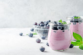 Two glasses of blueberry yogurt with blueberries on a light gray stone background. Front view, copy space, horizontal image