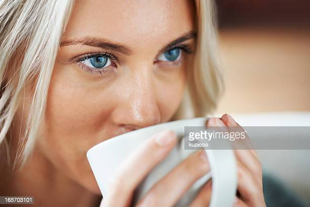 Blue-eyed, young woman drinking tea