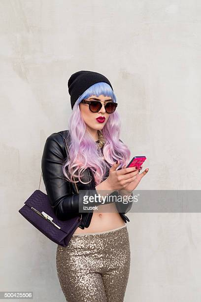 Blue-pink hair carefree girl texting on smart phone outside