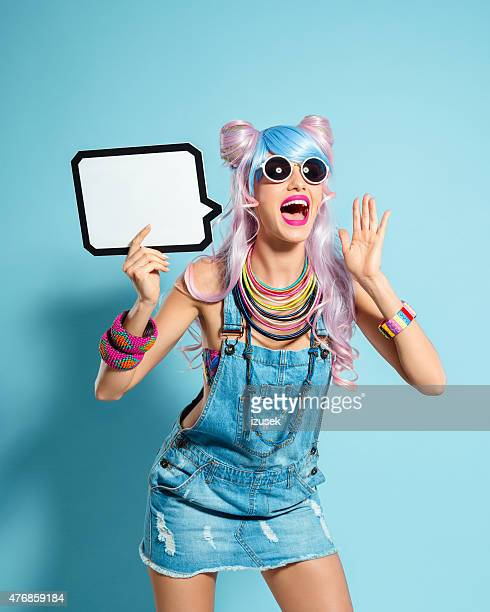 Blue-pink hair girl in funky manga outfit holding speech bubble