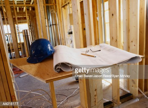 Blueprint and a Hard Hat Inside a Building Frame : Stock Photo