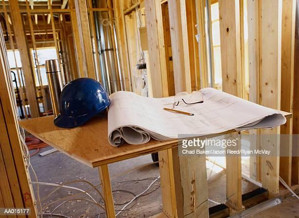 Blueprint and a Hard Hat Inside a Building Frame