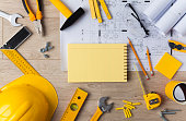Blueprints and Construction tools on wooden background