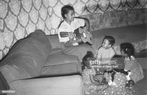 Blues and folk singer/song writer Elizabeth Cotten sings to children in a photo session shot from her debut Folkways Records album 'Folksongs And...