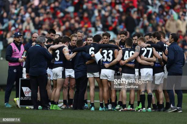 Blues coach Brendon Bolton speaks to his players at the break during the round 20 AFL match between the Essendon Bombers and the Carlton Blues at...