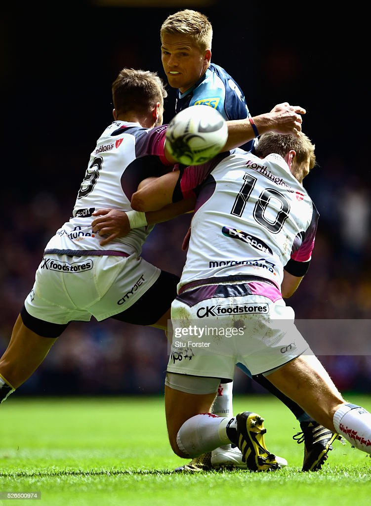 Blues fly half Gareth Anscombe is tackled by Rhys Webb (l) and Dan Biggar of the Ospreys during the Guinness Pro 12 match between Cardiff Blues and Ospreys at Principality Stadium on April 30, 2016 in Cardiff, United Kingdom.