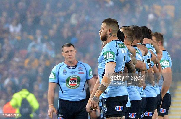 Blues players embrace as their captain Paul Gallen watches on during game three of the State of Origin series between the Queensland Maroons and the...