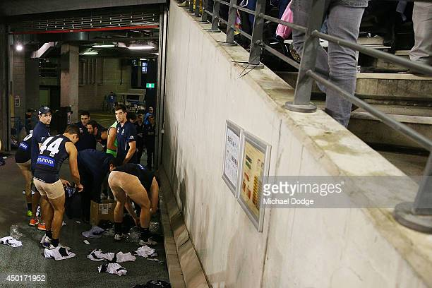 Blues players get changed into the correct coloured shorts going from white shorts to blue during the round 12 AFL match between the Geelong Cats and...