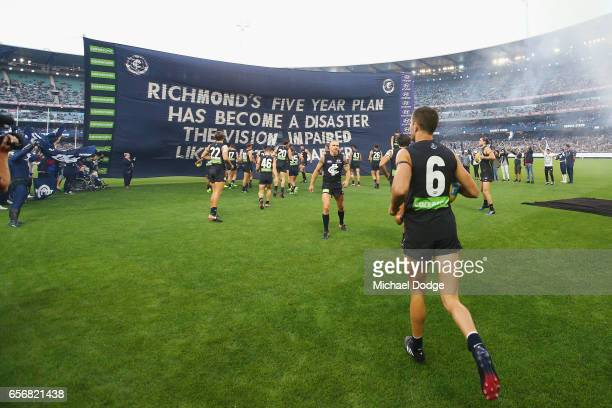 Blues players run to their banner during the round one AFL match between the Carlton Blues and the Richmond Tigers at Melbourne Cricket Ground on...