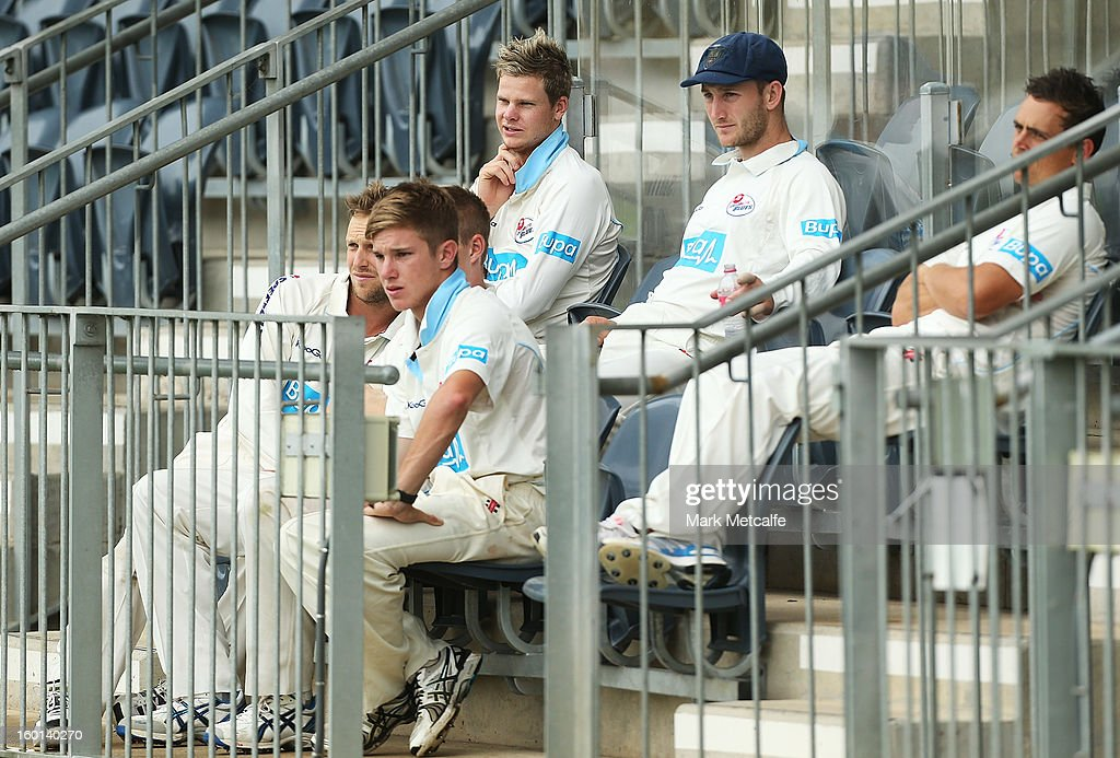Blues players wait in the stands as rain delays the start of play on day four of the Sheffield Shield match between the New South Wales Blues and the Western Australia Warriors at Bankstown Oval on January 27, 2013 in Sydney, Australia.