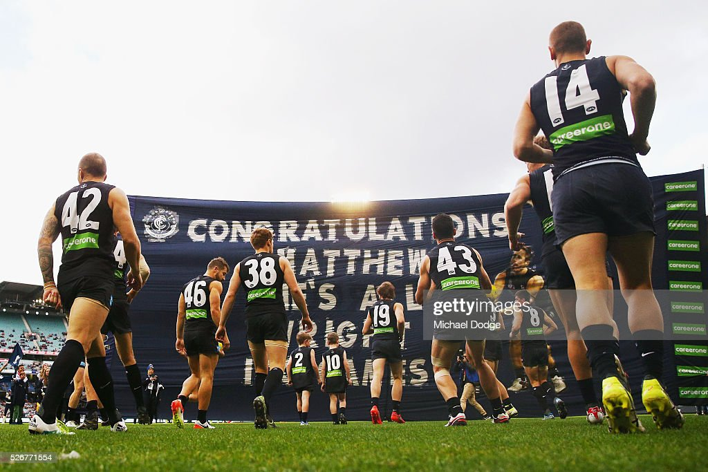 Blues players walk to their banner during the round six AFL match between the Carlton Blues and the Essendon Bombers at Melbourne Cricket Ground on May 1, 2016 in Melbourne, Australia.
