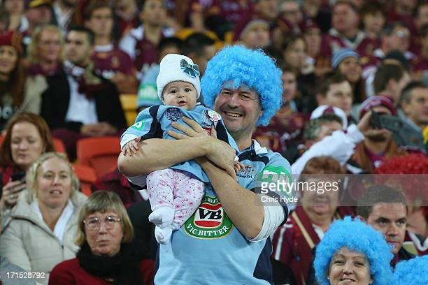 Blues supporter holds his baby before the start of game two of the ARL State of Origin series between the Queensland Maroons and the New South Wales...
