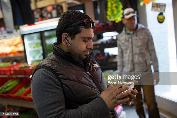 A bluetooth headset in his ear grocery store owner Somu Timsina checks messages on his smartphone in his shop's produce section Winooski Vermont...