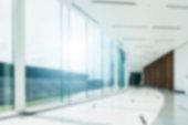 Blur background inside office hallway interior with glass wall window