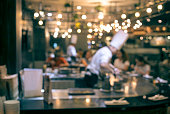 Blur chef cooking in restaurant with  customer sitting
