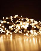 Blur Christmas lights on dark  golden background. Defocused Christmas garland, copyspace