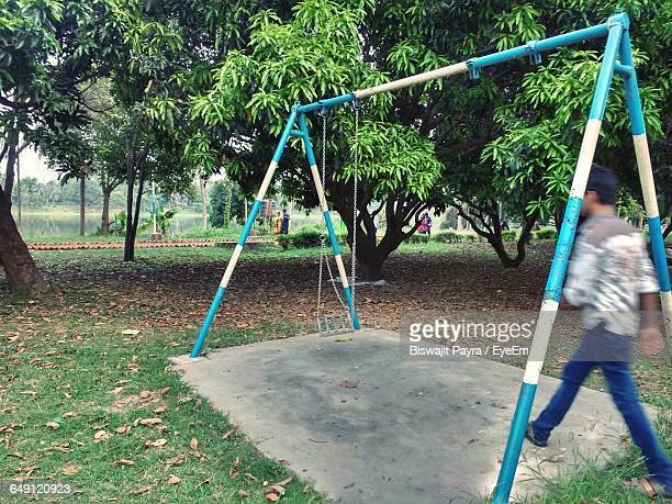 Blur Image Of Man Walking By Swing In Park