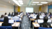 Blur image of many people are training in the big training room with computer.