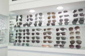 Blur Sunglasses on display shelves in glasses store background