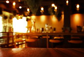 blur top of brown wood table with dark light cafe or bar interior background