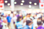 Blurred background : crowd of people in expo fair with bokeh light .