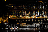Blurred background of dark bar with bottles of alcohol and with barman essentials in the foreground