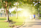 Blurred background of people running in park with burst light