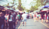 Blurred background : people shopping at market fair in sunny day, blur background with bokeh.