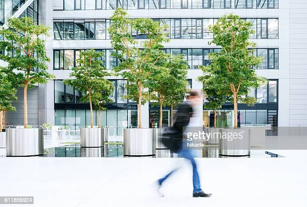blurred business man walking in a business park