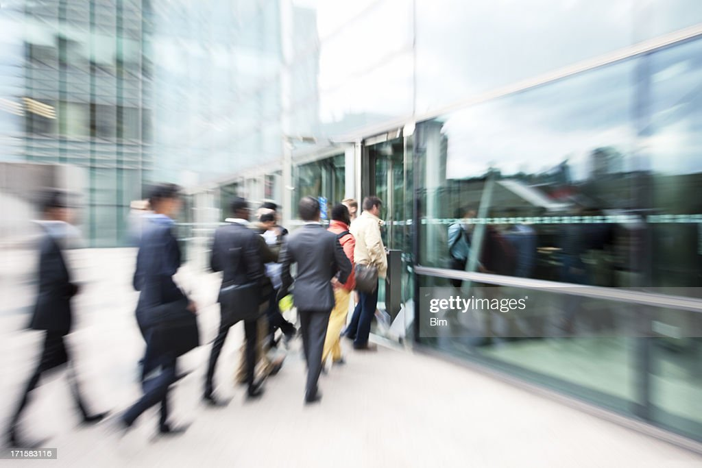 Business People Entering Office Building Through Glass Doors
