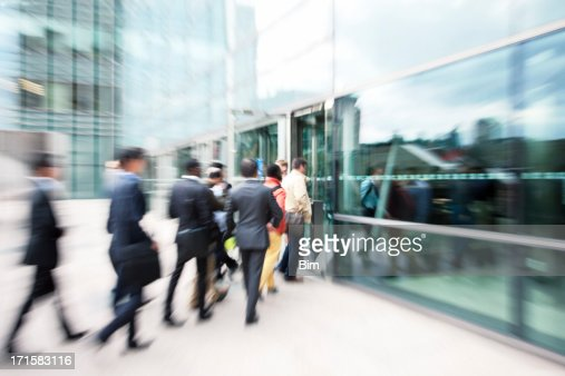 Blurred Business People Entering Office Building Through Glass Doors