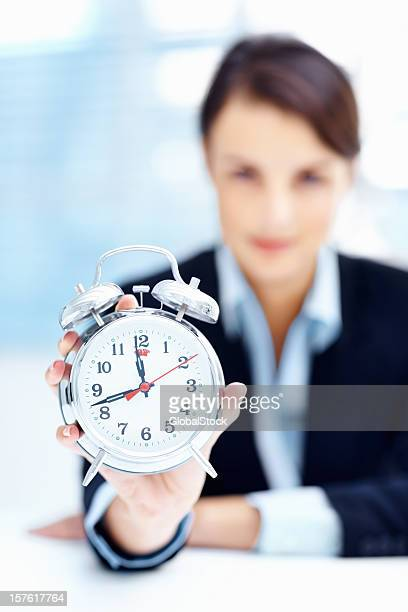 Blurred business woman showing you an alarm clock