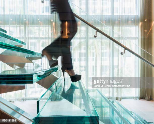 Blurred businesswoman climbing stairs in office