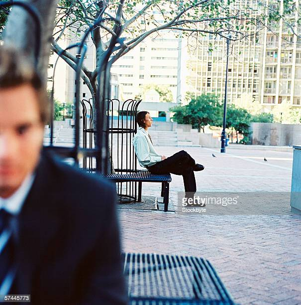 blurred close-up of a young businessman sitting on a park bench