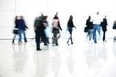 Blurred Commuters Walking in White Corridor