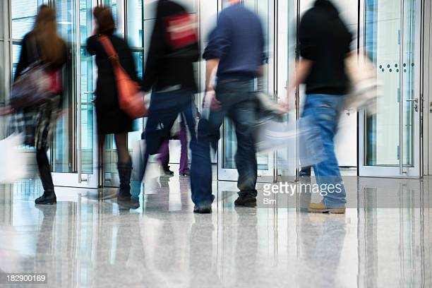 Blurred Commuters Walking Through Glass Doors
