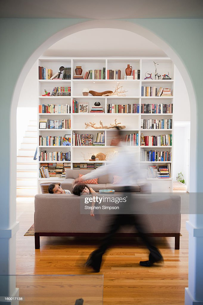 blurred father walks by girls on the couch : Stock Photo