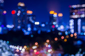 blurred focus of cityscape at night in bangkok with tower and road, twilight sky