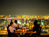 Blurred focus of rooftop restaurant with people dinning at night