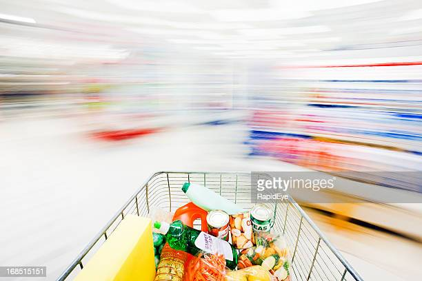 Blurred, ghostlike supermarket aisles with racing, filled shopping cart